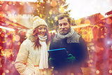happy couple walking with tablet pc in old town