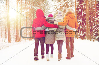 group of happy men and women in winter forest
