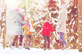 group of happy friends playing snowballs in forest