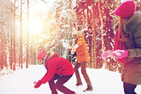 happy friends playing snowball in winter forest