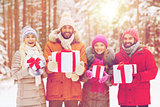 happy friends with gift boxes in winter forest