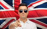 man in shades pointing finger over brittish flag