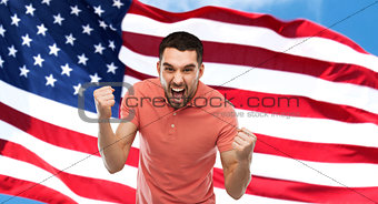 angry man showing fists over american flag