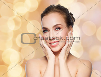 beautiful woman touching face over holidays lights