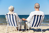 senior couple sitting on chairs at summer beach