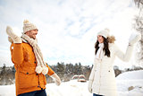 happy couple playing snowballs in winter