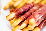 close up of grissini bread sticks with prosciutto