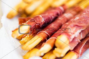 close up of grissini bread sticks with prosciutto