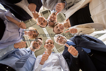 business people snowing thumbs up at office