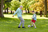 old man and boy playing football at summer park