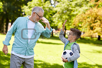 old man and boy with soccer ball making high five