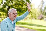 happy senior man waving hand at summer park