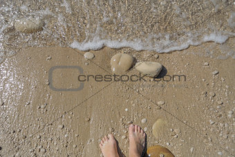 Top down view of feet waiting for a wave