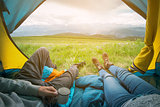 Two people lying in tent with a view of mountains. Altay, Russia.