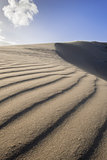 Wind blowing sand over dune
