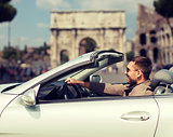 happy man driving cabriolet car over city of rome