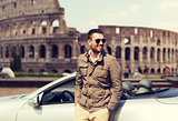 happy man near cabriolet car over coliseum