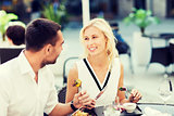happy couple eating dinner at restaurant terrace