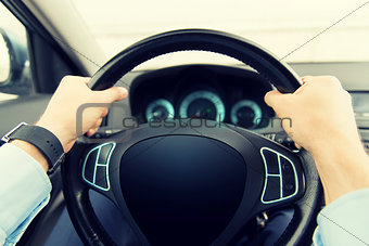 close up of man driving car with computer screen