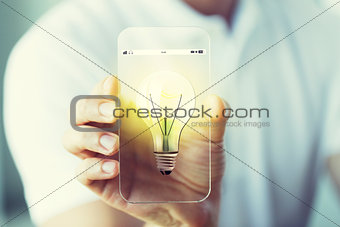 close up of hand with light bulb on smartphone