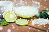 body lotion in bowl and limes on wood