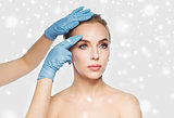 surgeon or beautician hands touching woman face