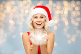 happy woman in santa hat with fairy dust on hands