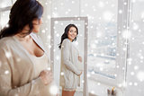 happy pregnant woman looking to mirror at home
