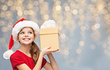 smiling girl in santa hat with christmas gift box
