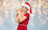 smiling girl in santa helper hat with teddy bear