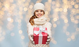smiling girl in winter clothes with christmas gift