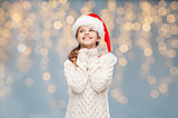 girl in santa hat dreaming over christmas lights