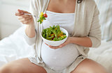 close up of pregnant woman eating salad at home