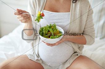 close up of pregnant woman eating salad at home
