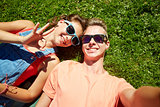 happy teenage couple taking selfie on summer grass