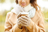 close up of happy woman with coffee in autumn park
