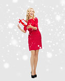 happy woman in red dress with christmas gift box