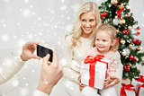 family taking picture with smartphone at christmas