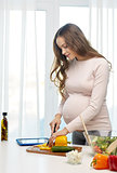 happy pregnant woman preparing food at home