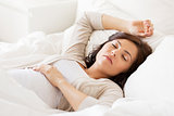 happy pregnant woman sleeping in bed at home