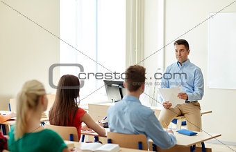 group of students and teacher with papers or tests