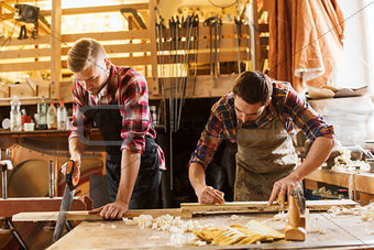 carpenters working with saw and wood at workshop