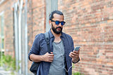 man with earphones and smartphone walking in city