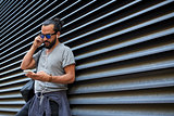 man with earphones and smartphone on city street