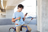 man with smartphone and earphones on bicycle