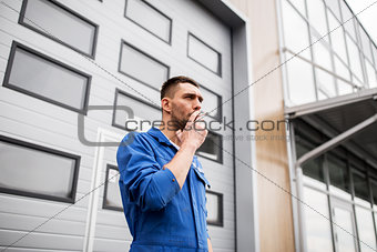 auto mechanic smoking cigarette at car workshop