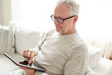 senior man with tablet pc at home