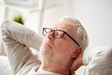 senior man in glasses relaxing on sofa