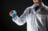 close up of doctor holding flask with cure vaccine