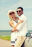 happy man and woman hugging near car at sea